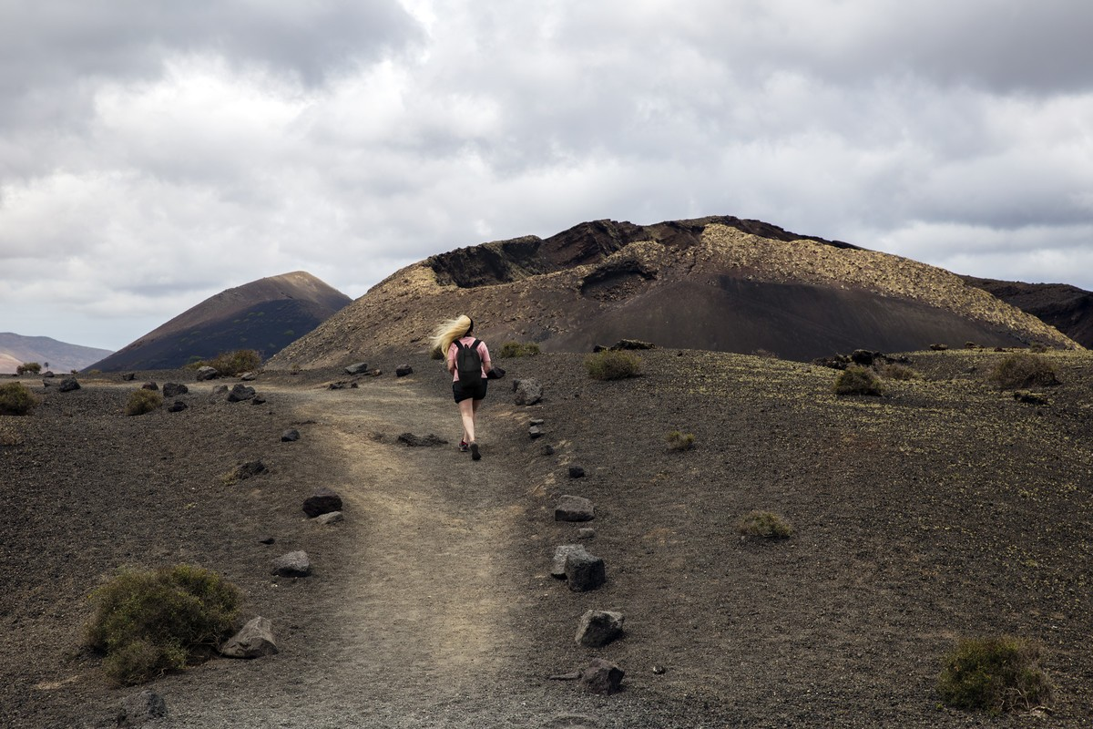 Woman walking on a path near a volcano in Timanfaya, Lanzarote